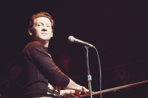 Jerry Lee Lewis, U.S. rock and roll singer and pianist, playing the piano during a concert performance on stage at the Rainbo