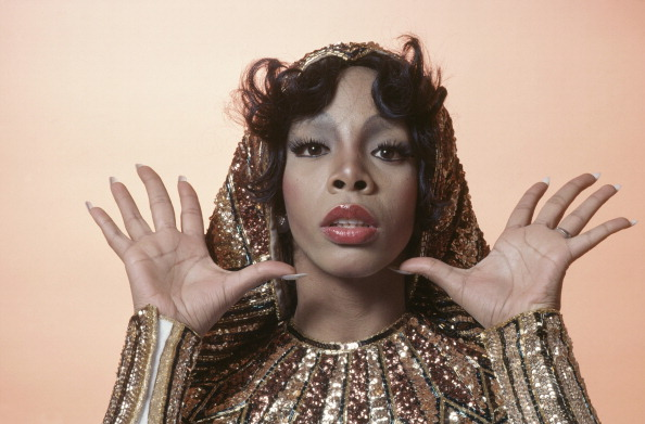 Headshot of Donna Summer, US singer-songwriter, posing in a studio portrait, with her hands raised, open-palmed, either side