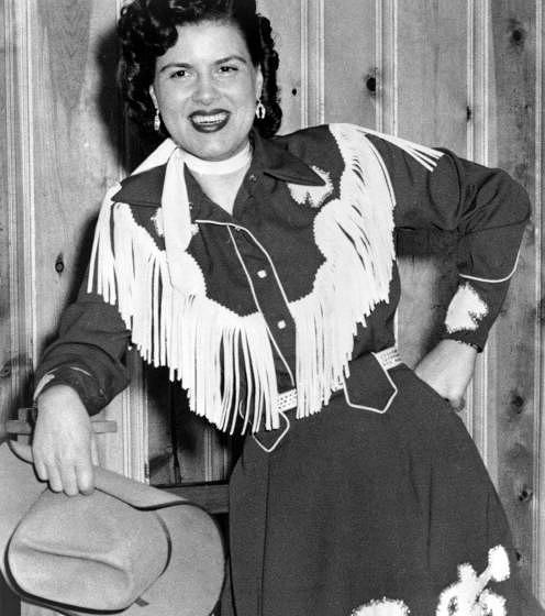 CIRCA 1958:  Country musician Patsy Cline plays the piano wearing a fringed dress and holding a cowboy hat in circa 1958. (Ph