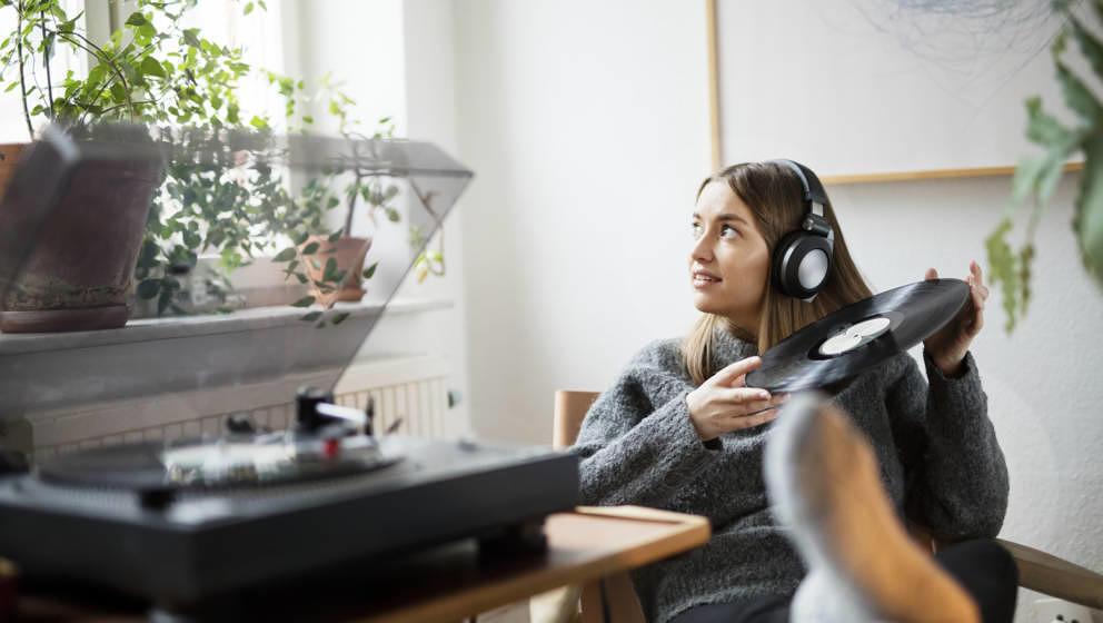 Frau hört Vinylplatte mit Kopfhöhrern