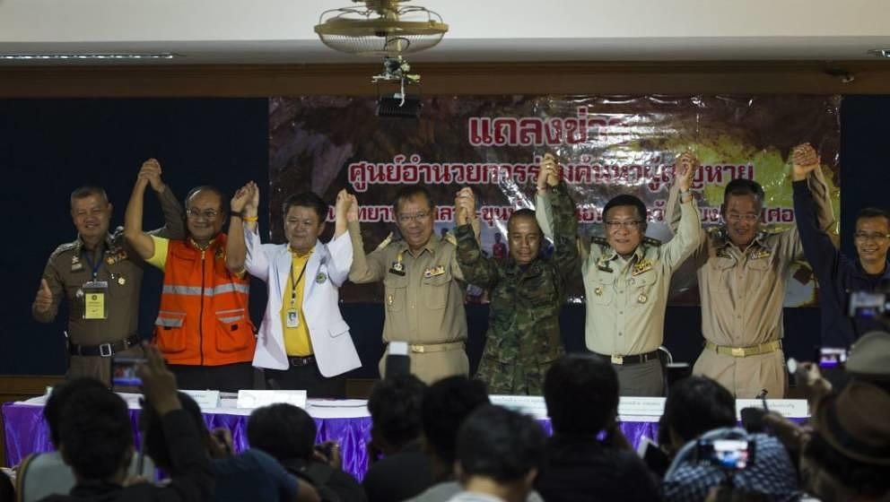 Chiang Rai Governor Narongsak Osotthanakorn (4L) and mission team celebrate after a press conference at a makeshift press cen