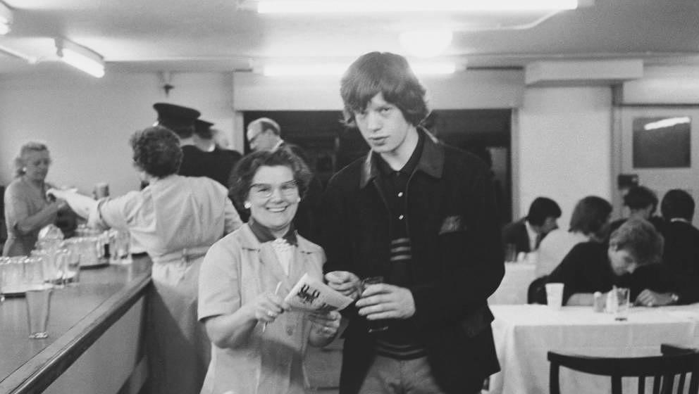 Rolling Stones singer Mick Jagger posing for a picture and signing an autograph for a tea lady in a canteen, mid 1960s. (Phot