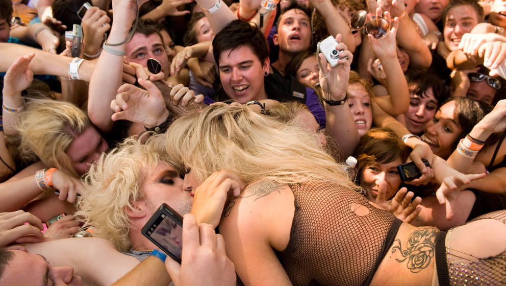 Justin Tranter of Semi-Precious Weapons and Lady Gaga pause for a kiss while crowd-surfing as Semi-Precious Weapons performs