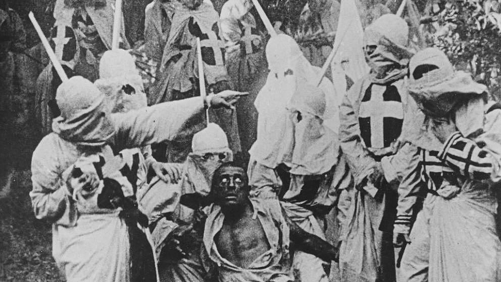 Black and white photograph of a group of Klansmen surrounding freedman Gus (played by white actor Walter Long in blackface) i