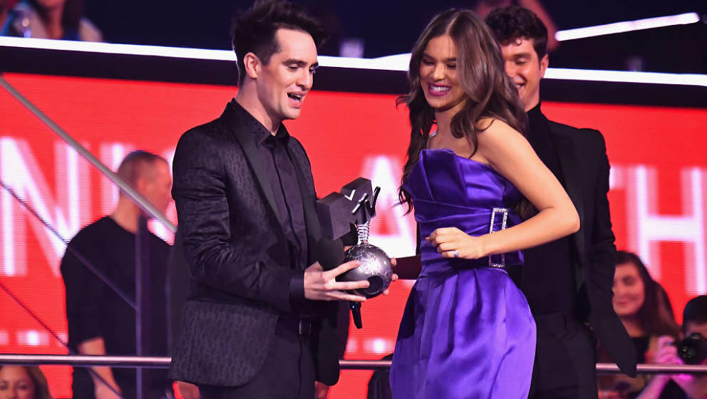 BILBAO, SPAIN - NOVEMBER 04:  Brendon Urie of Panic! at the Disco collects an award from Hailee Steinfeld on stage during the