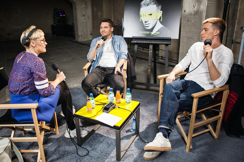 Diese drei Personen sitzen im Stuhlkreis und geben ein Interview