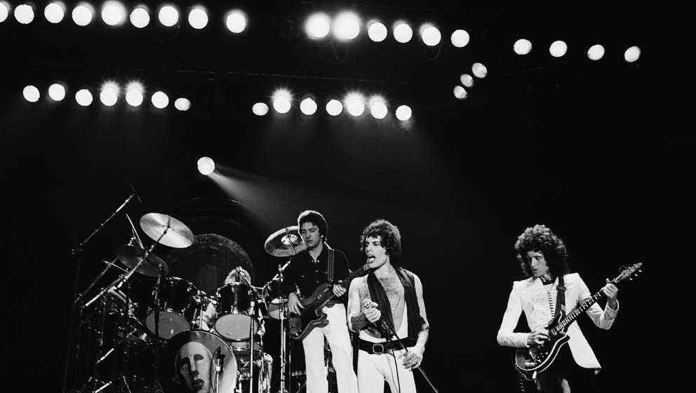 Queen (from left: drummer Roger Taylor (partially obscured by his drumkit), bassist John Deacon, singer Freddie Mercury (1946