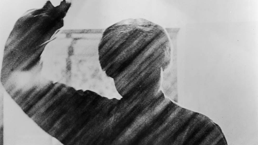 View of a silhouetted figure holding a knife in the famous shower scene from the film, 'Psycho,' directed by Alfred Hitchcock
