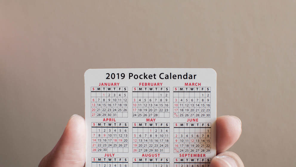Holding a pocket new year calendar on a white background