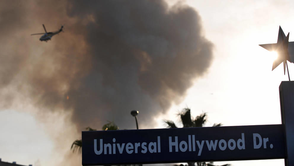 A helicopter flies over burning structures at Universal Studios, in Universal City, California, on June 01, 2008. MOre than 1