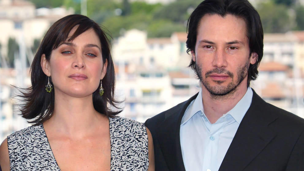 US actor Keanu Reeves and Canadian-born actress Carrie-Anne Moss pose for photographers on a terrace of the Palais des festiv