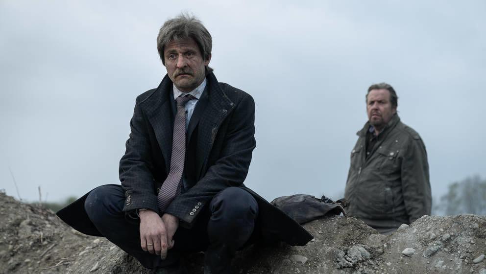 """Szene aus der zweiten Staffel """"Hindafing"""": Scheinbar traurig betrachtet Alfons Zischl (Maximilian Brückner, links) das Desaster, das er ausgelöst hat. Hinter ihm steht Sepp Goldhammer (Andreas Giebel)."""