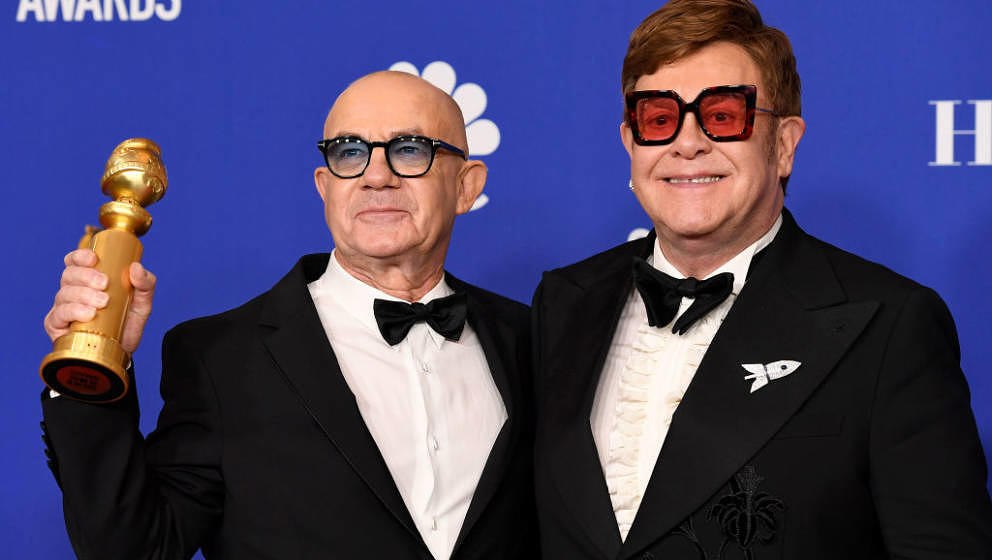BEVERLY HILLS, CALIFORNIA - JANUARY 05: 77th ANNUAL GOLDEN GLOBE AWARDS -- Pictured: Bernie Taupin (L) and Elton John, winner