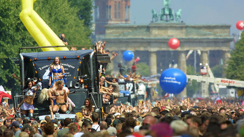 BERLIN, GERMANY - JULY 12:  People dance around trucks blaring techno music near the Brandenburg Gate during the annual Love