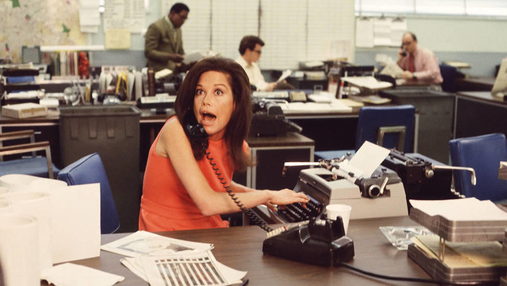 American actress Mary Tyler Moore mouths surprise on the telephone while simultaneously typing as others work in the backgrou