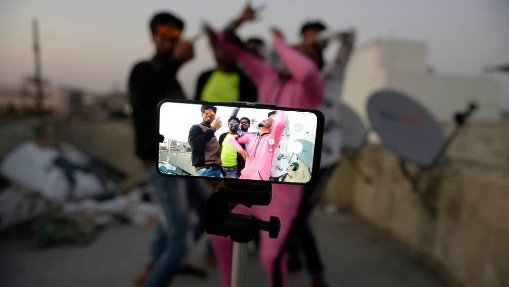Youths act in front of a mobile phone camera while making a TikTok video on the terrace of their residence in Hyderabad on Fe