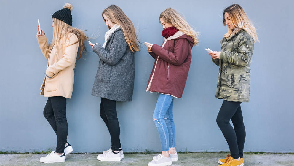 Gijon, Asturias, Spain, four young women texting with her smartphones