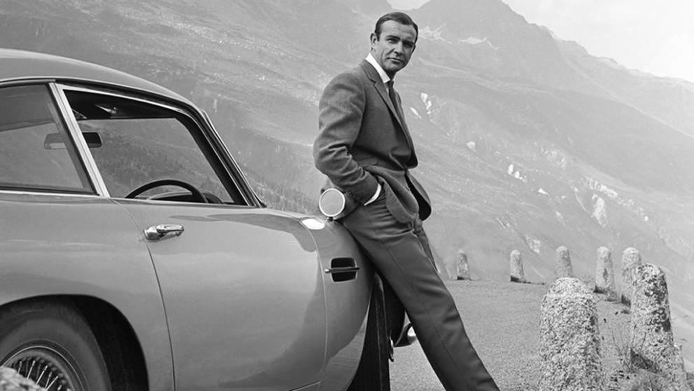 1964:  Actor Sean Connery poses as James Bond next to his Aston Martin DB5 in a scene from the United Artists release 'Goldfi
