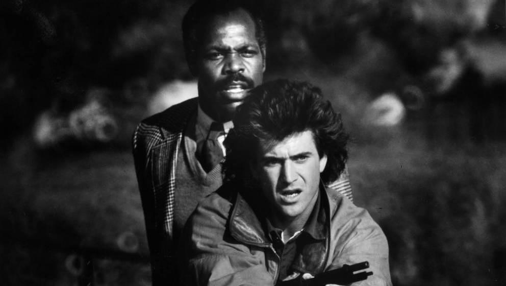 Danny Glover stands behind Mel Gibson in a scene from the film 'Lethal Weapon', 1987. (Photo by Warner Brothers/Getty Images)