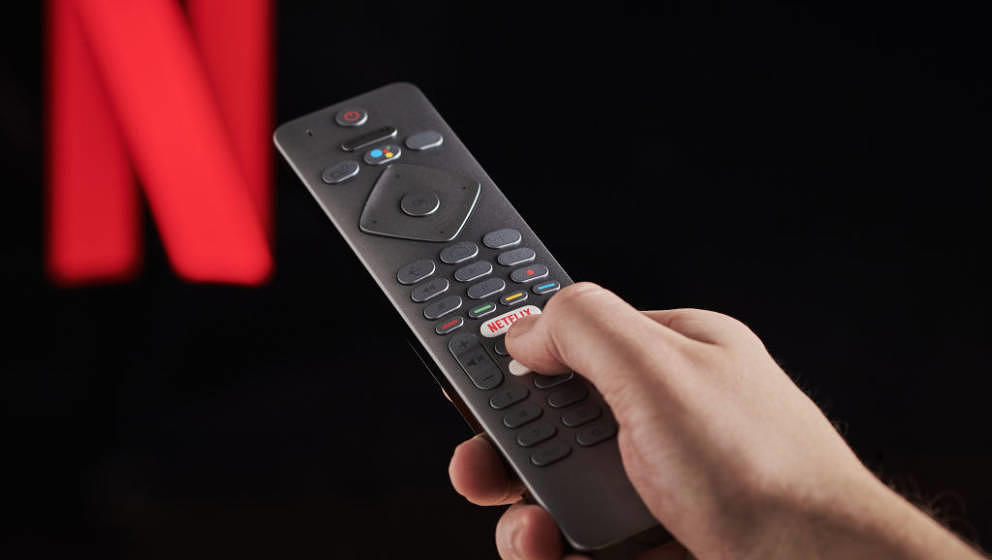 Detail of a mans hand pressing the Netflix button on a TV remote control, with Netflix streaming on a television in the backg