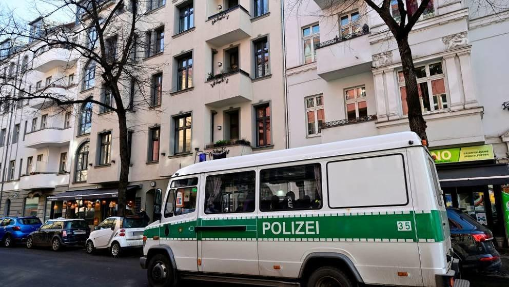 A police van stands parked in front of a building in Berlin's Neukoelln district that was searched earlier during raids again