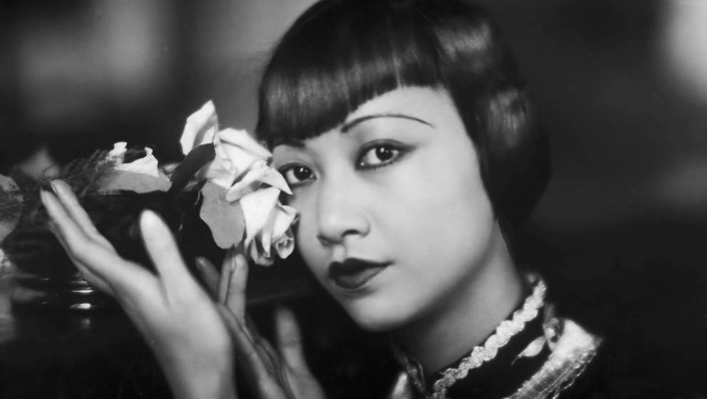 Der amerikanische Filmstar Anna May Wong (1905 - 1961) posiert mit einer abgeschnittenen Rose, ca. im Jahr 1935.