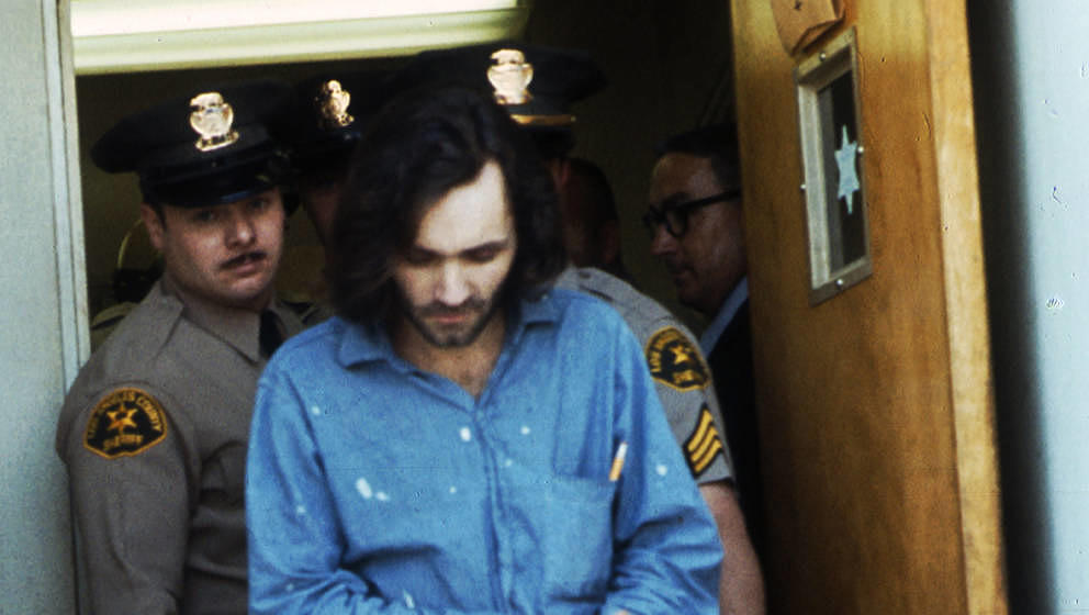 American criminal and cult leader Charles Manson (1934 - 2017) is escorted by Los Angeles County sheriffs to a police van to
