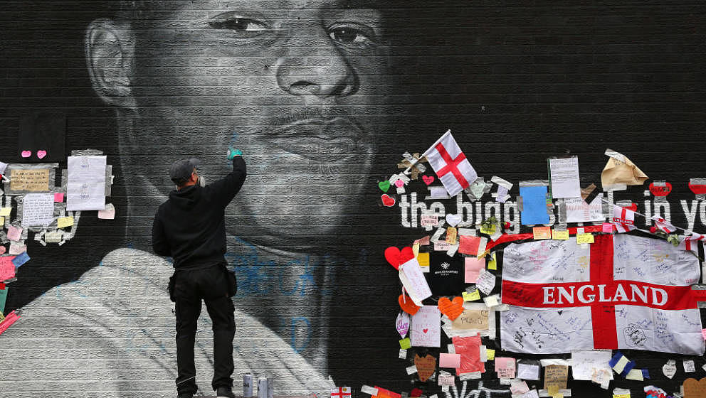 MANCHESTER, ENGLAND - JULY 13:  A defaced mural of Marcus Rashford is repaired by the artist Akse P19 on July 13, 2021 in Man