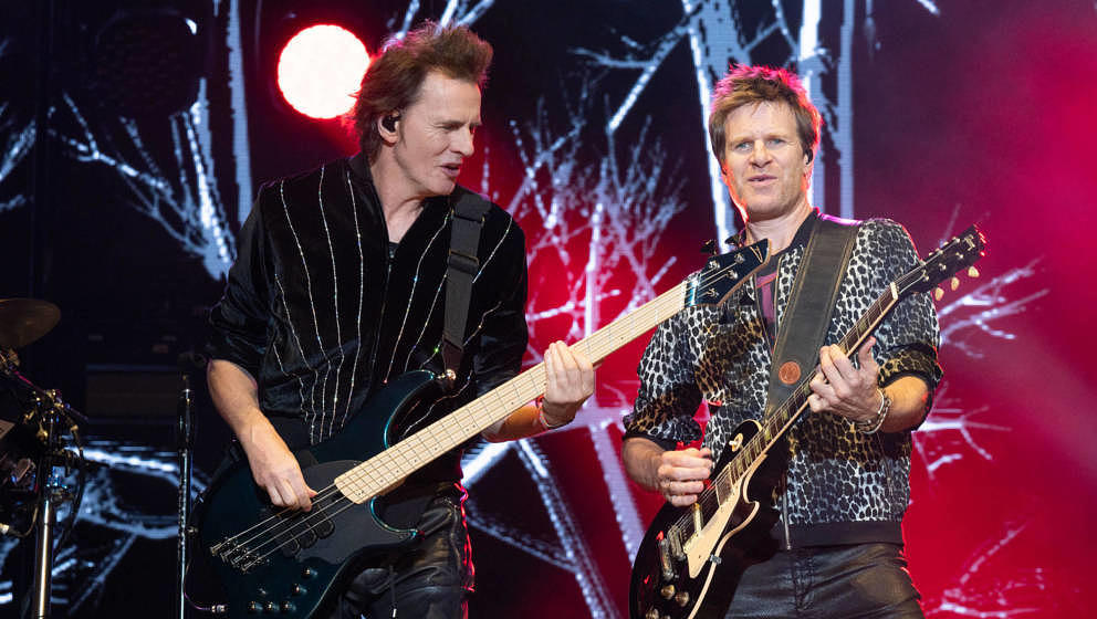AUSTIN, TEXAS - OCTOBER 10: Bassist John Taylor (L) and touring guitarist Dominic Brown of Duran Duran perform live on stage